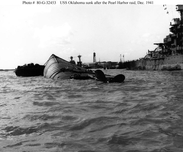 The capsized hull of USS Oklahoma (BB-37), with a barge alongside to support rescue efforts, probably on 8 December 1941. USS Maryland (BB-46) is at right, and USS California (BB-44) is in the center distance. (Navy)